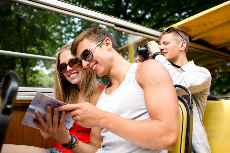 Smiling couple with book traveling by tour bus royalty free stock photography