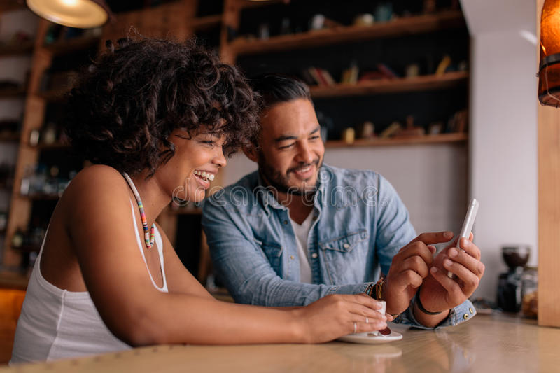 Smiling couple at cafe using mobile phone stock image