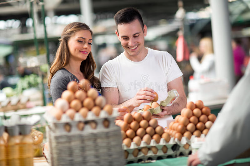 Smiling couple choosing eggs at the market stock images