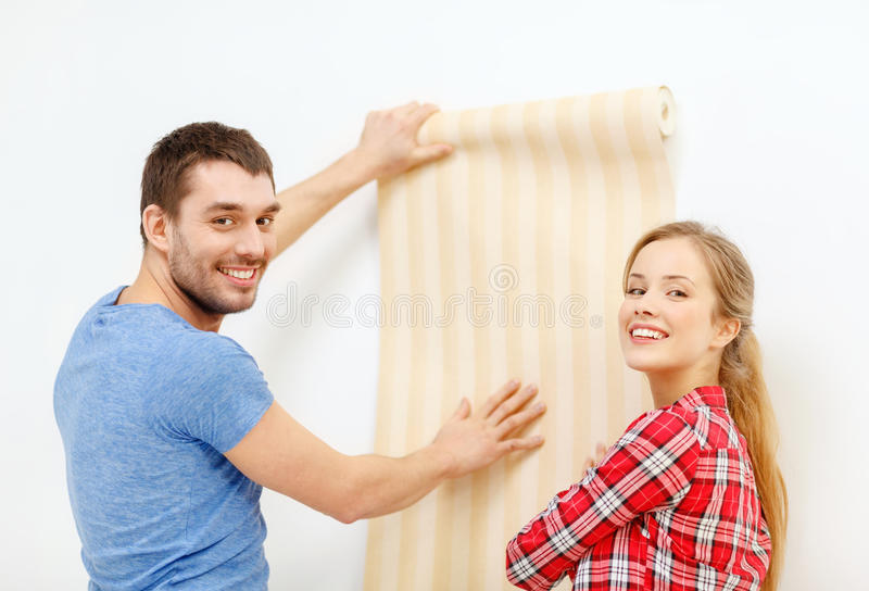 Smiling couple choosing wallpaper for new home. Repair, interior design, building, renovation and home concept - smiling couple choosing wallpaper for new home royalty free stock photos