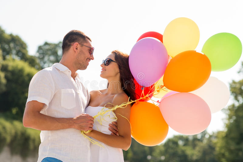 Smiling couple in city. Love, wedding, summer, dating and people concept - smiling couple wearing sunglasses with balloons hugging in park stock image
