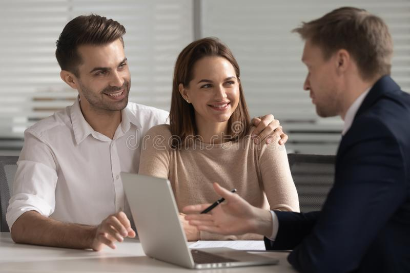 Smiling couple consulting with financial advisor or real estate agent. stock photo