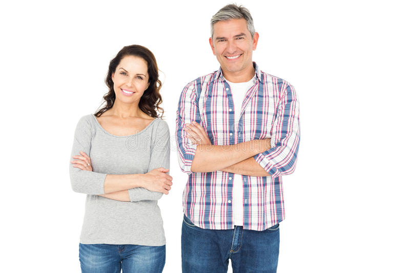 Smiling couple with crossed arms looking the camera. On white background stock photos