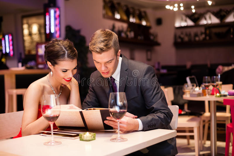 Smiling couple decide what to order stock image