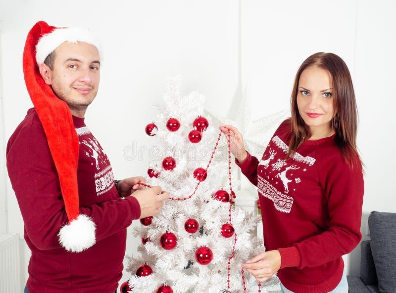 Smiling couple decorates Christmas tree royalty free stock photos