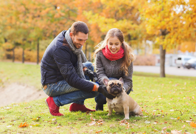 Download Smiling Couple With Dog In Autumn Park Stock Photo - Image of owners, lifestyle: 46443544