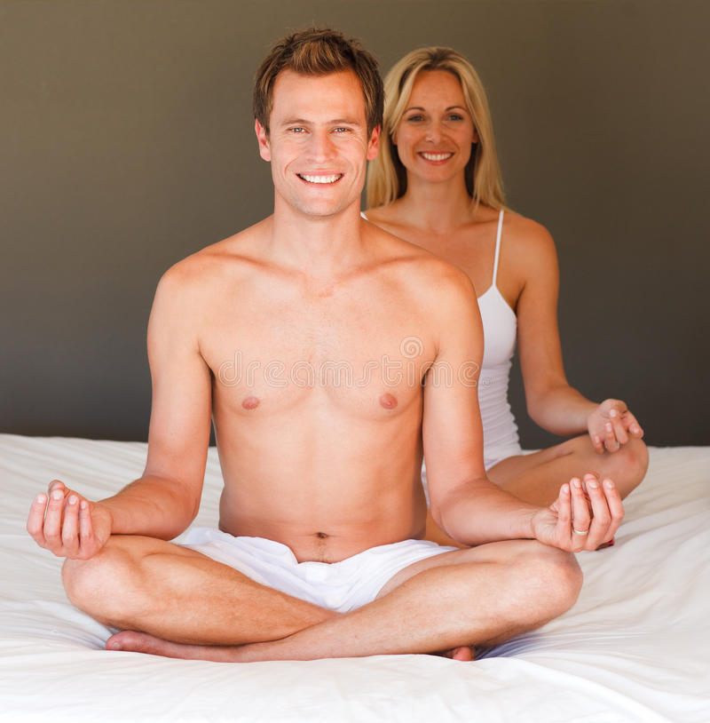 Smiling couple doing exercises on bed. Smiling young couple doing exercises on bed royalty free stock image