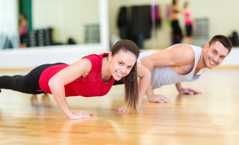 Smiling couple doing push-ups in the gym royalty free stock image