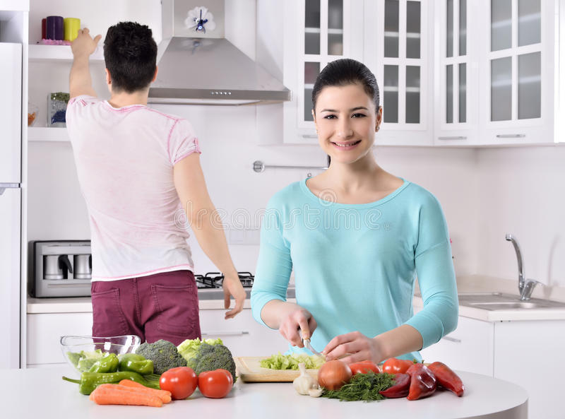 Smiling couple eat salad in the kitchen stock images