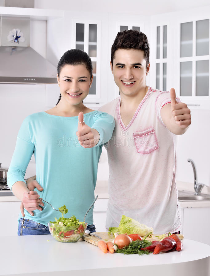 Smiling couple eat salad in the kitchen stock photography