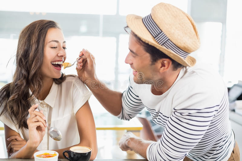 Smiling couple eating dessert. In cafe stock photography