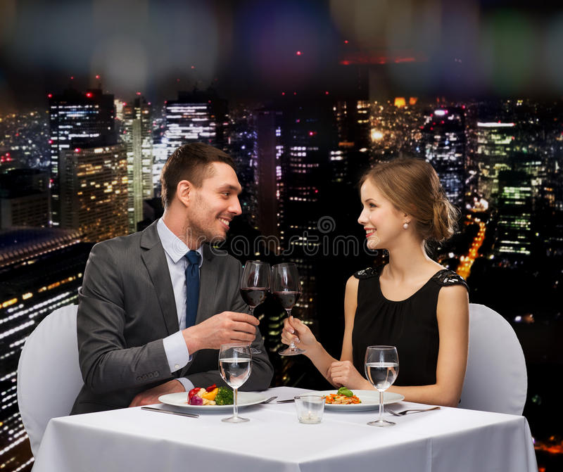 Smiling couple eating main course at restaurant. Restaurant, couple and holiday concept - smiling couple eating main course with red wine at restaurant stock photo