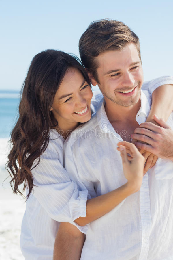Smiling couple embracing each other on the beach stock image