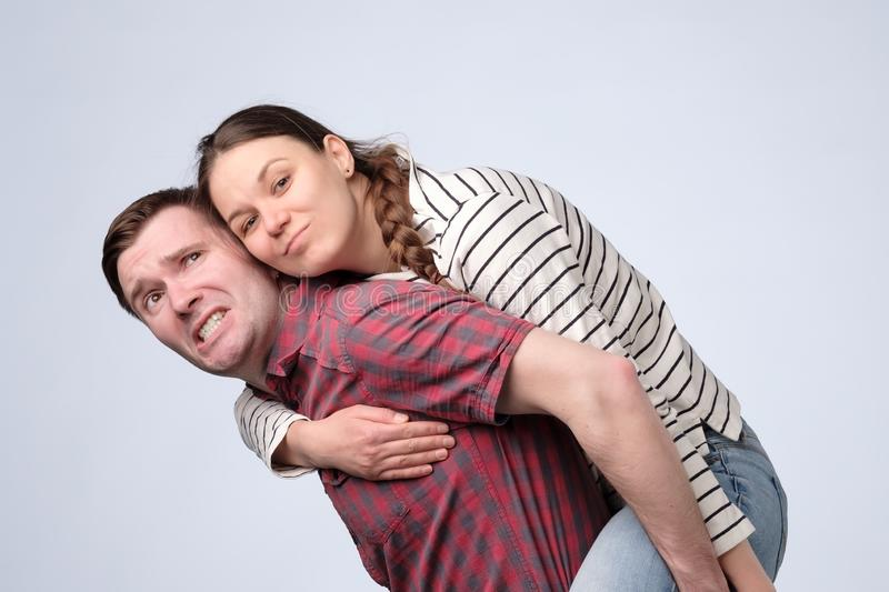 Smiling couple embracing in piggy back and looking at camera on white background royalty free stock photography