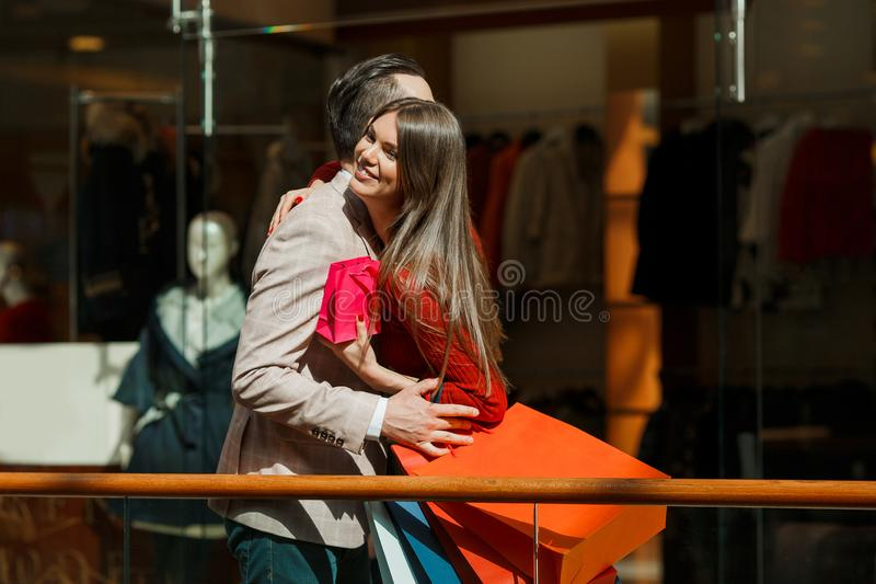Couple embracing at shopping mall stock images