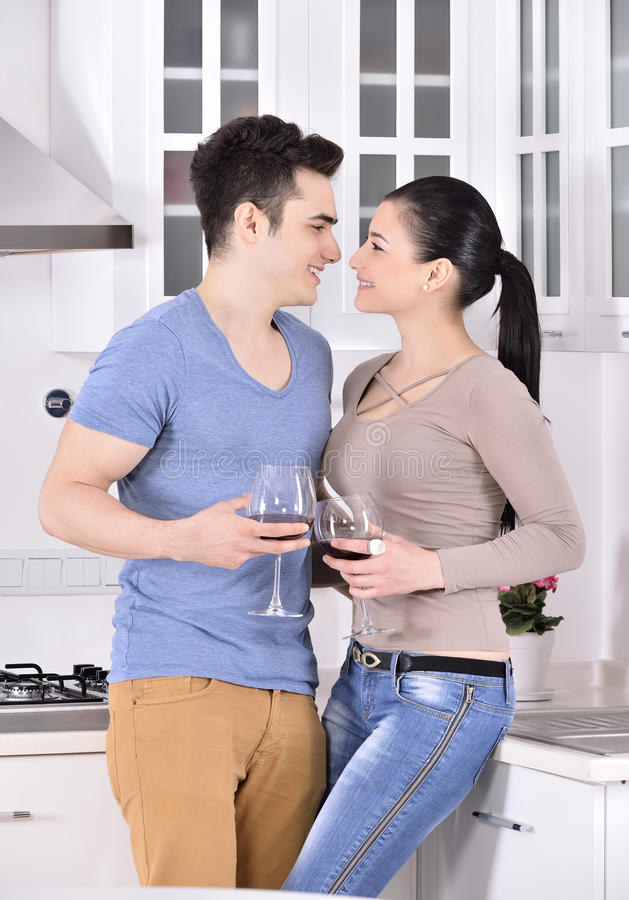 Smiling couple enjoying red vine in the kitchev stock photos