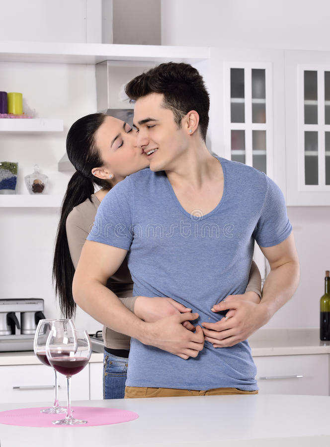 Smiling couple enjoying red vine in the kitchev stock photo