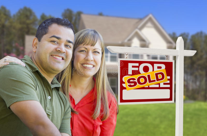Smiling Couple in Front of Sold Real Estate Sign and House. Happy Mixed Race Couple in Front of Sold Home For Sale Real Estate Sign and House stock images