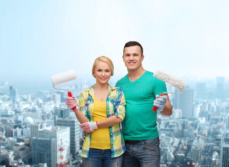 Smiling Couple In Gloves With Paint Rollers Stock Photo
