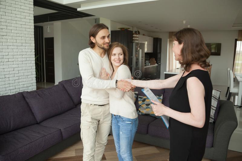 Smiling couple handshaking real estate agent buying or renting h stock image