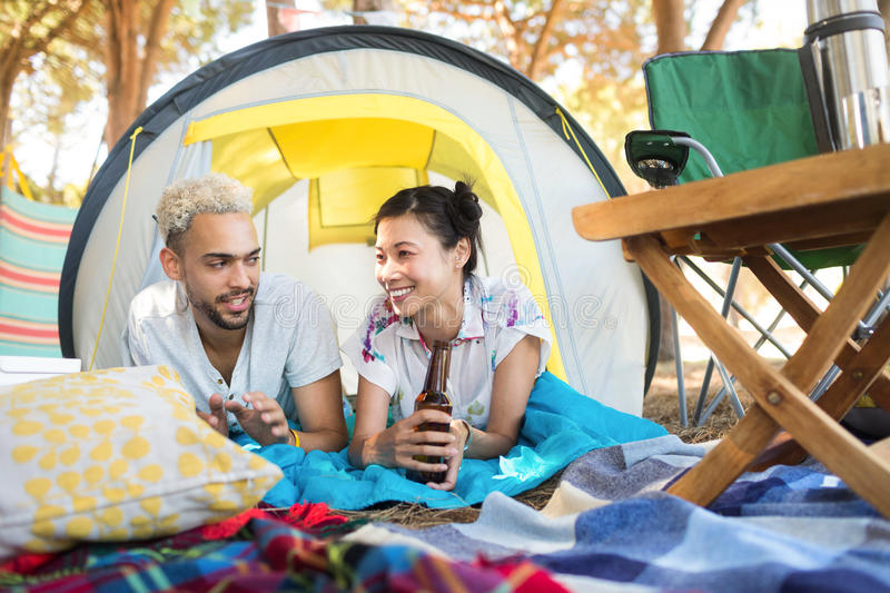 Smiling couple having drink while relaxing tent. At campsite royalty free stock photo