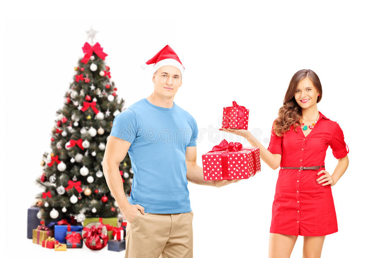 Smiling couple holding gifts and posing in front of a christmas royalty free stock photo
