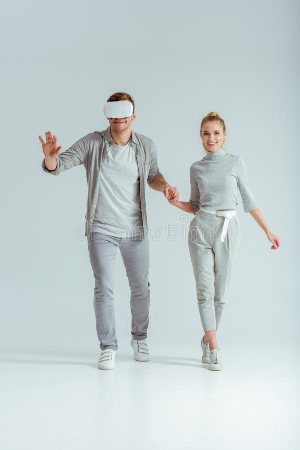 Smiling couple holding hands while man experiencing virtual reality. On grey background stock photos