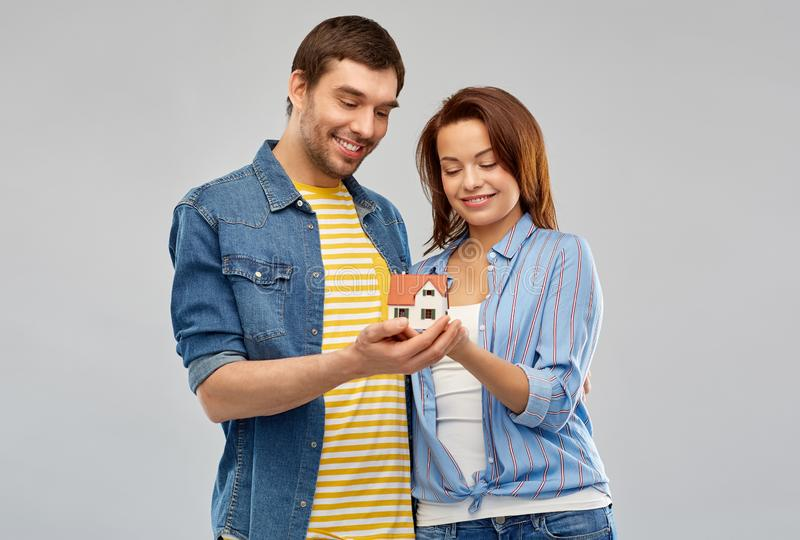 Smiling couple holding house model. Real estate, family and mortgage concept - smiling couple holding house model over grey background royalty free stock photo
