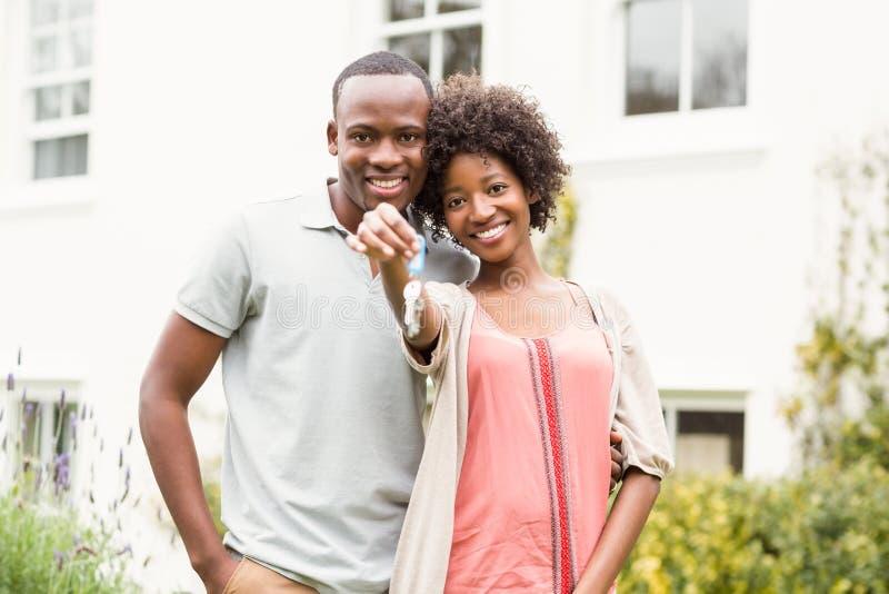 Smiling couple holding keys stock photos