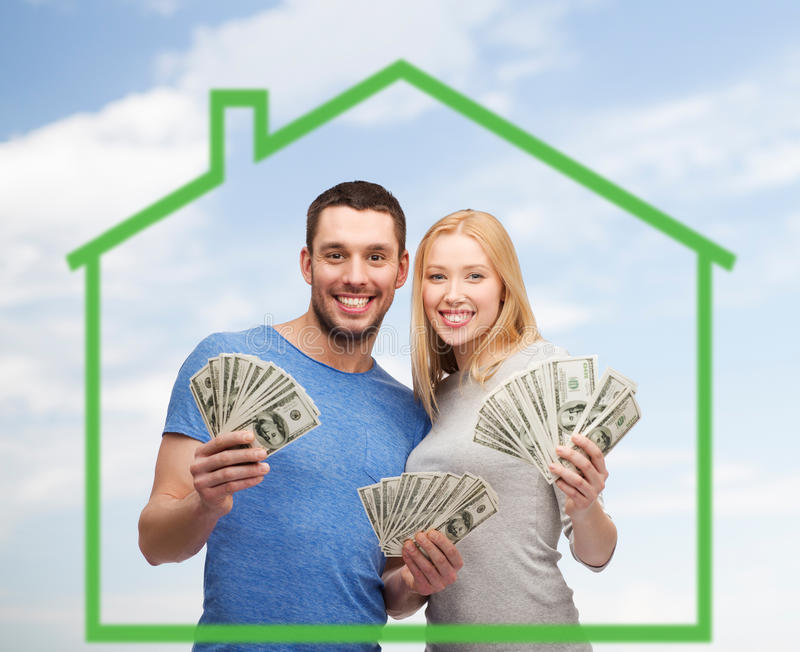 Smiling couple holding money over green house stock photos