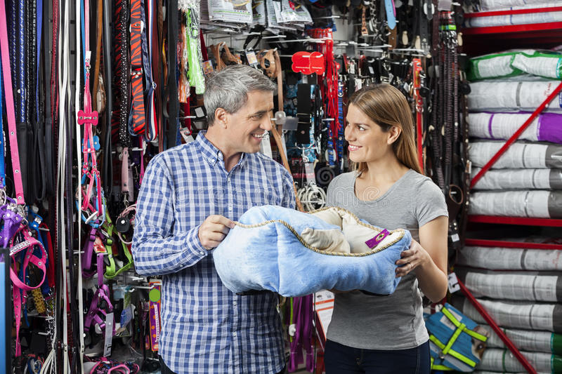 Smiling Couple Holding Pet Bed At Store. Smiling couple looking at each other while holding pet bed in store royalty free stock photo