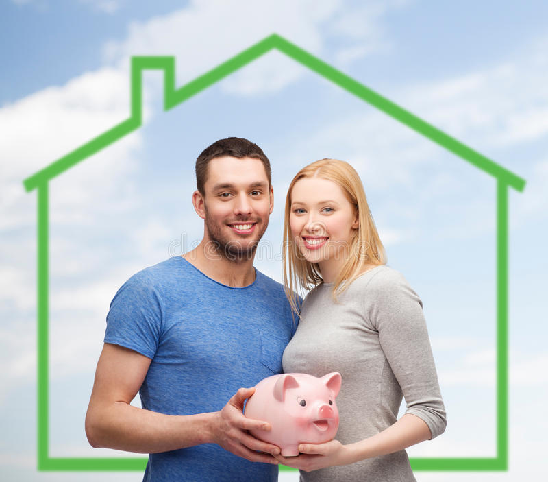 Smiling couple holding piggy bank over green house stock photo