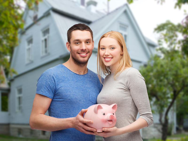 Smiling couple holding piggy bank over house stock photo