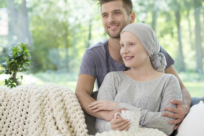 Smiling couple at home. Husband supporting sick wife after chemo stock photography
