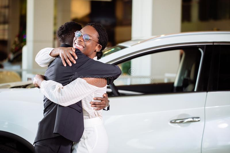 Couple collecting new car from salesman on lot royalty free stock photos