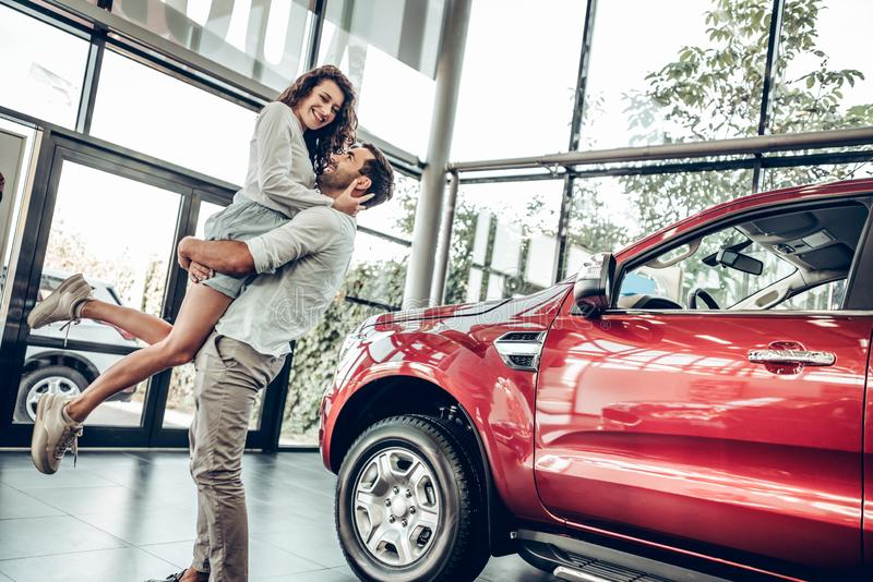 Smiling couple hugging and smiling at camera at new car showroom. Man is holding women in his arms. bottom view stock images