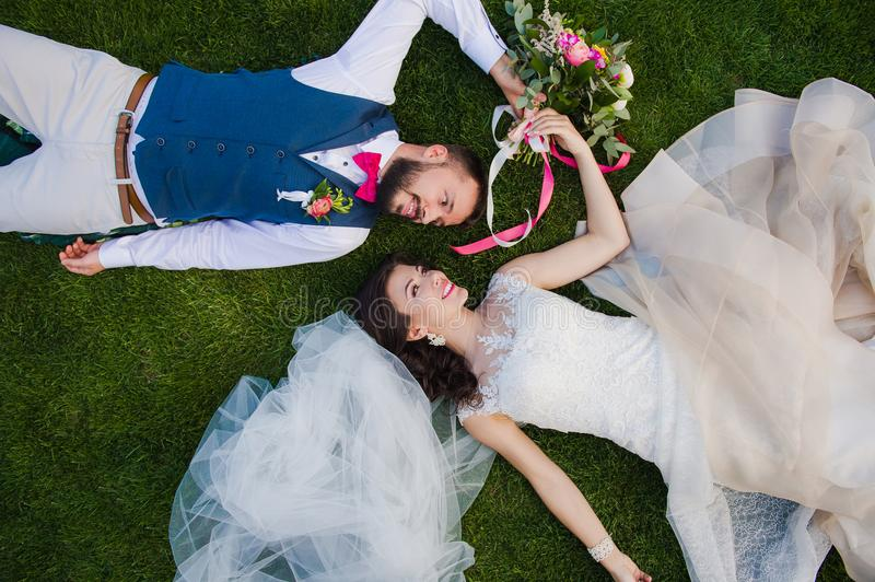 Smiling couple laying on the grass royalty free stock photos
