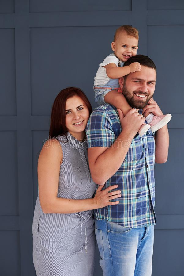Smiling couple with little daughter posing at camera in studio stock images