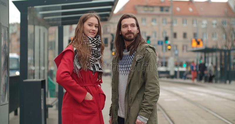 Smiling couple looking away while waiting at tram stop in a city. stock photos