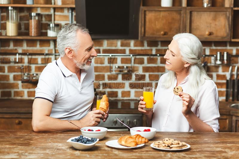 Couple drinking juice at the kitchen royalty free stock image