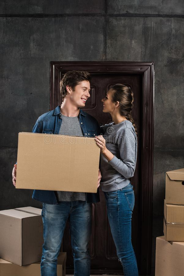 Smiling couple looking at each other while holding cardboard box together at new home, moving. Home concept royalty free stock photo