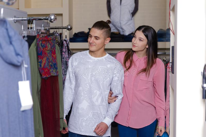 The young couple considers clothes in shop. Young nice couple in shop with purchases royalty free stock photography