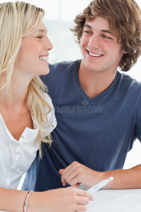 Smiling couple looking at one another as they hold a pregnancy