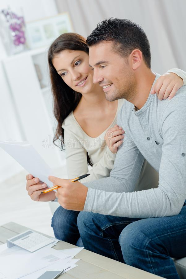 Smiling couple looking at paperwork royalty free stock image