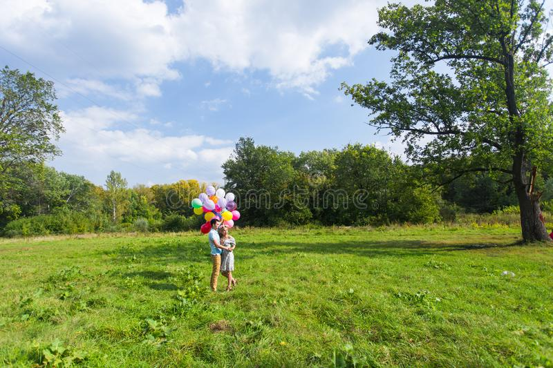 Smiling couple in love with balloons in nature stock image