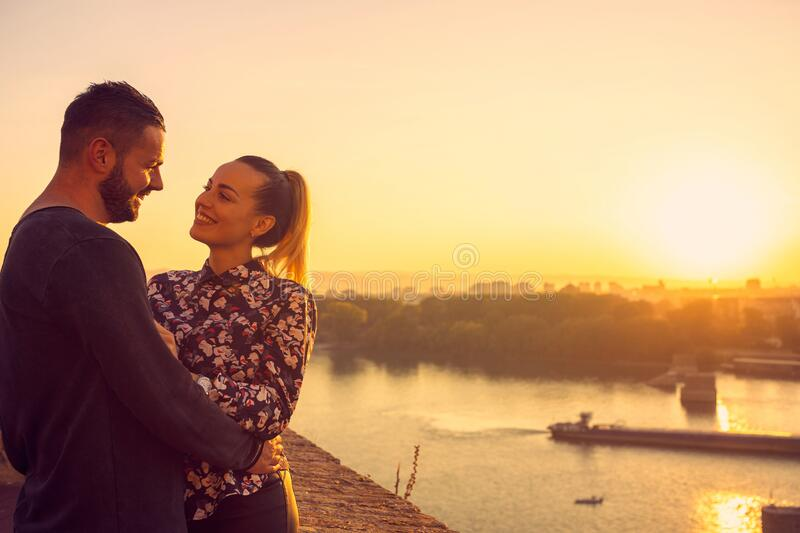 Smiling Couple in love, enjoying at the romantic moment at sunset royalty free stock image