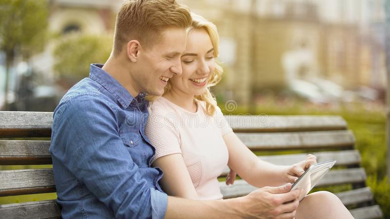 Smiling couple in love viewing photos from vacation on tablet, using mobile app stock photography