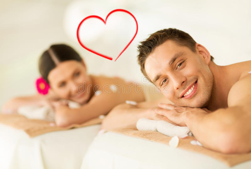 Smiling couple lying on massage table in spa salon stock images