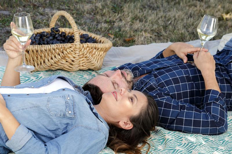 Smiling couple lying with wineglasses outdoor royalty free stock photography