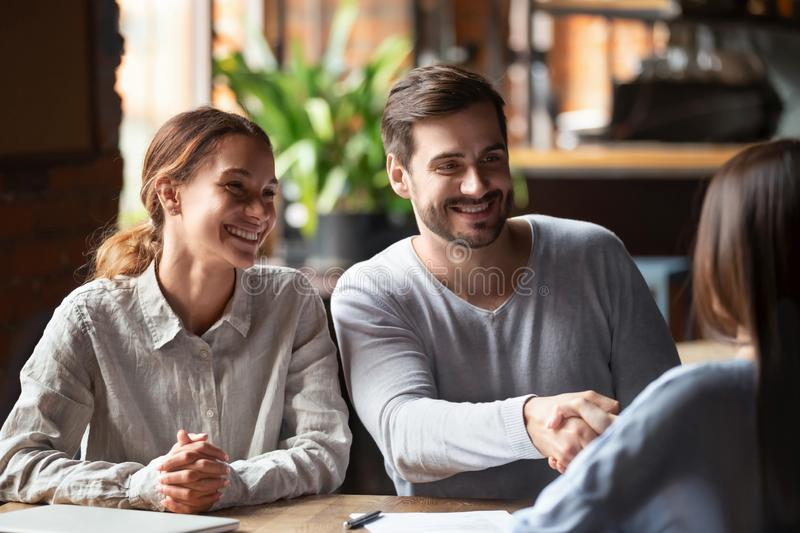 Smiling couple making deal, husband shaking hand of broker or realtor. Smiling couple at meeting, husband shaking hand of broker, financial advisor or agent in stock photography